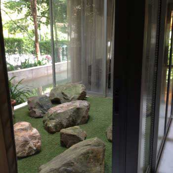 display of artificial green grass with artistic rock formation