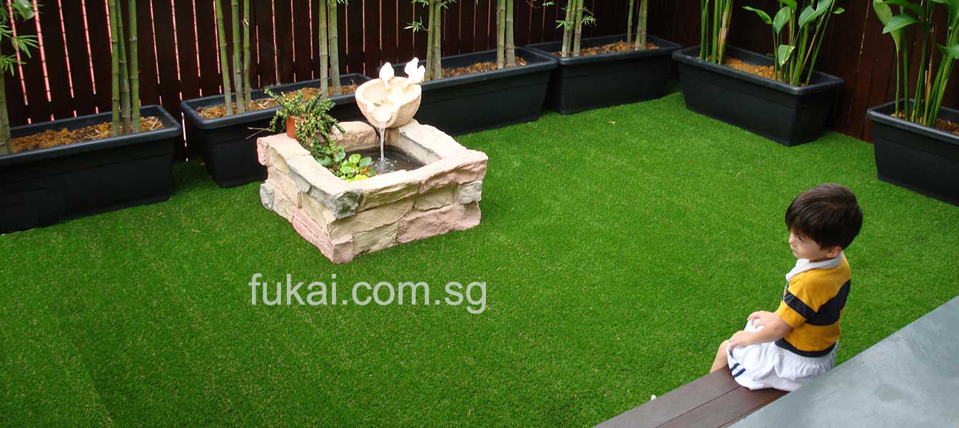 kid in the middle of beautiful artificial green grass landscape